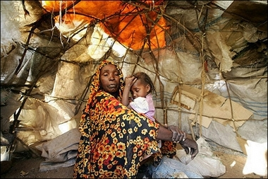 A displaced Sudanese woman sits with her daughter in their barrack at the Sakali Displaced Persons camp in Darfur city of Nyala, February 2007.
