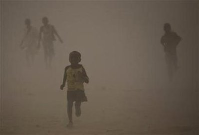 Refugees who fled the conflict in Sudan's western Darfur region run for shelter during a dust storm at Djabal camp near Gos Beida in eastern Chad June 19, 2008.
