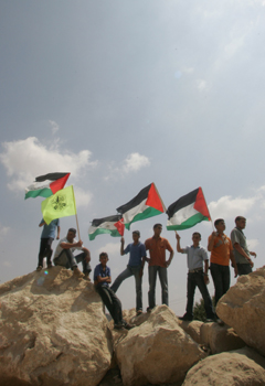 Demonstrators hold Palestinian and Fatah flags in front of Israeli soldiers