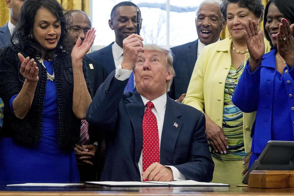 President Donald Trump holds up his pen after signing the Historically Black Colleges and Universities HBCU Executive Order, Tuesday, Feb. 28, 2017, in the Oval Office in the White House in Washington.